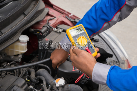 mechanic checking battery with multimeter