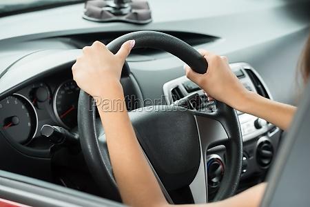 females hand holding steering wheel