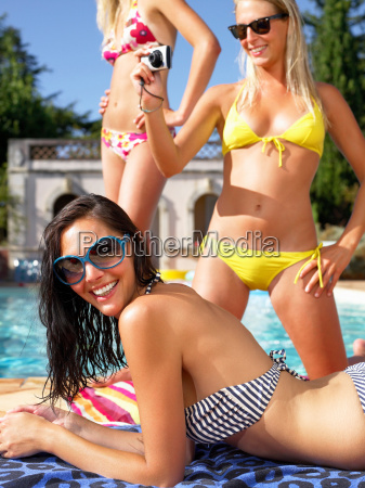 girlfriends taking pictures by the pool