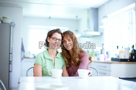 two women in kitchen with coffee