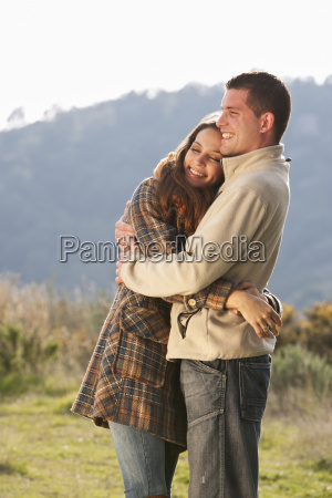 young couple embracing in rural scene
