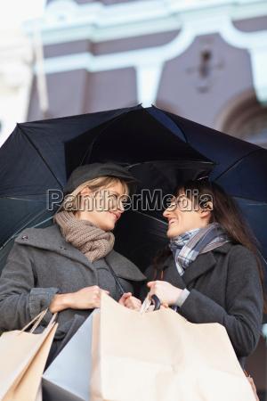 women under umbrellas on city street