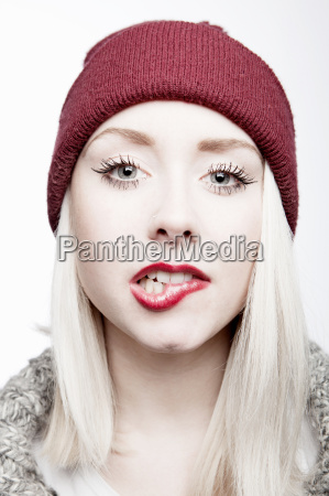 young woman wearing red hat biting