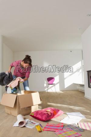 woman unpacking from cardboard box