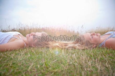 girls lying in field long hair