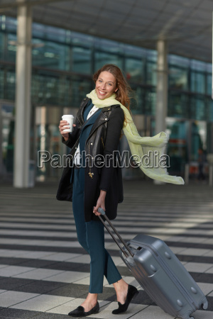 young woman at airport with wheeled