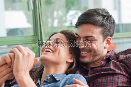 romantic young couple laughing on sofa
