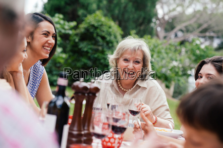 senior woman enjoying meal with family