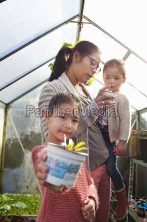 girl holding plant pot with mother