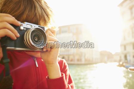 young boy exploring with camera venice