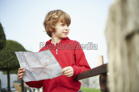 young boy holding map in park