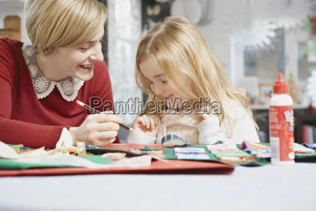 mother and daughter drawing at kitchen