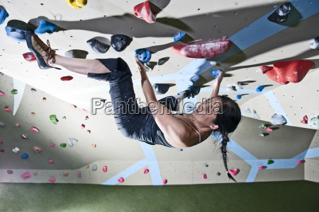 mature woman bouldering upside down on