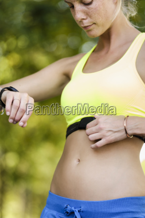 young female athlete checking heart rate