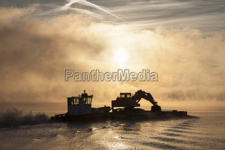 silhouette of excavator on barge