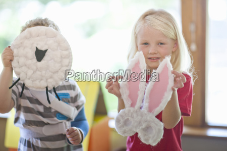 boy and girl holding up sheep