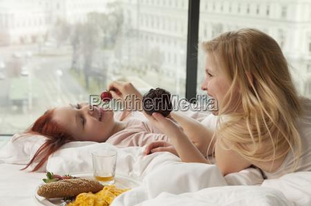 young women having breakfast in bed