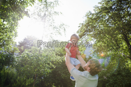 father holding up toddler son in
