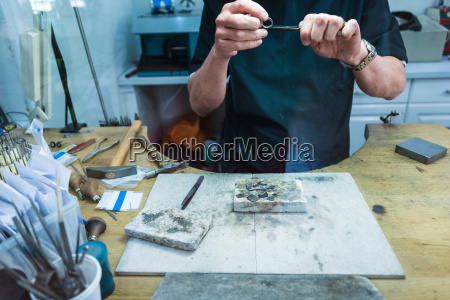cropped shot of jewellery craftsman filing