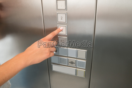 females hand pressing first floor button