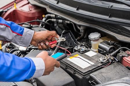 mechanic hands using multimeter for checking