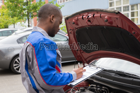 mechanic with clipboard in front of