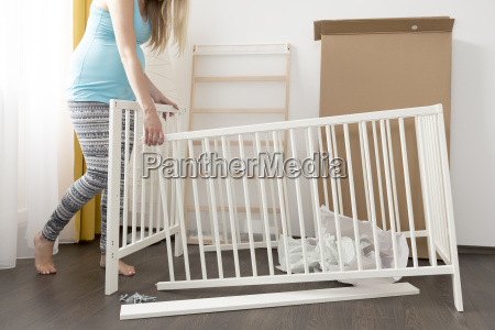 young pregnant woman assembling bed for