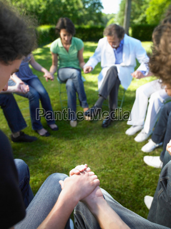 circle of people in rehab holding