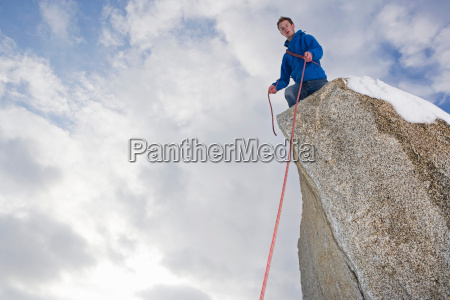 climber belaying on snow covered peak
