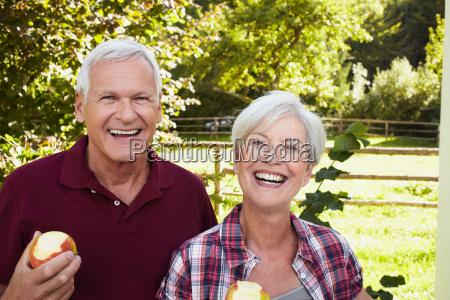 senior couple eating apples smiling
