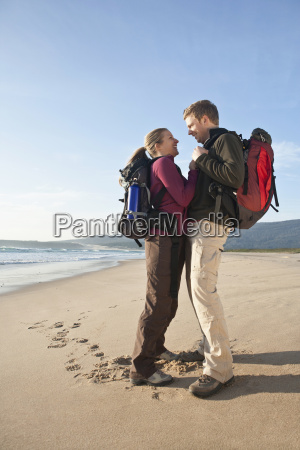 backpacking couple hugging at beach