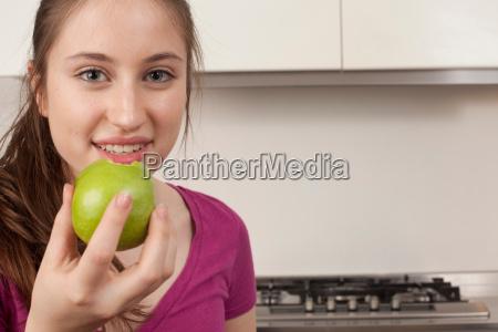 teenage girl eating an apple in