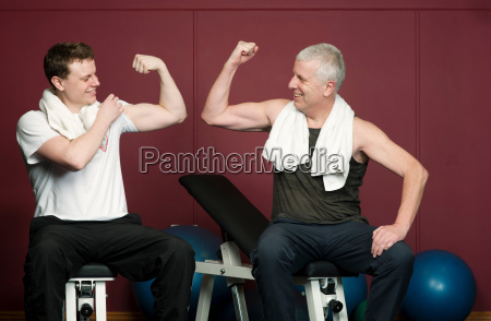 father and son flexing muscles in
