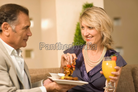 smiling couple eating hors douerves