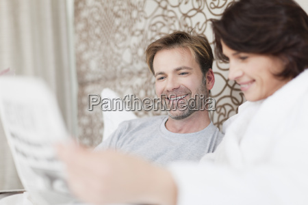 smiling couple using laptop in bed