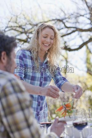 woman serving boyfriend salad outdoors