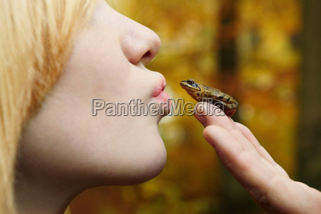 girl kissing tiny frog in forest