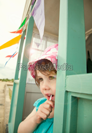 girl eating lollipop in doorway