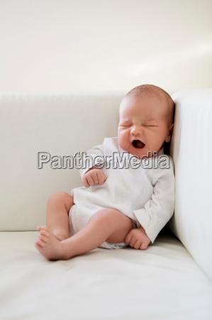 infant yawning on sofa