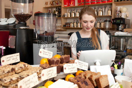 young woman using cash register in