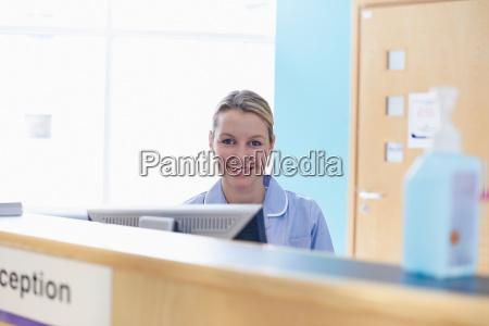 nurse sitting at reception desk