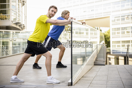 two, men, leaning, and, stretching, legs - 18216780