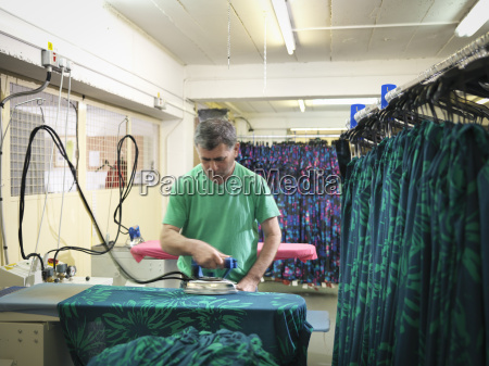 garment worker ironing clothing in clothing