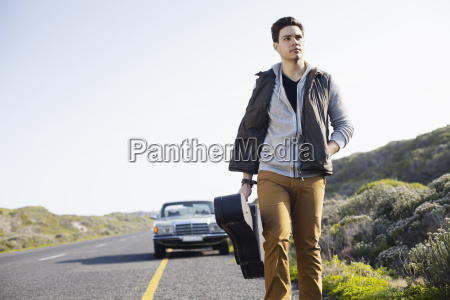 young man walking along road with