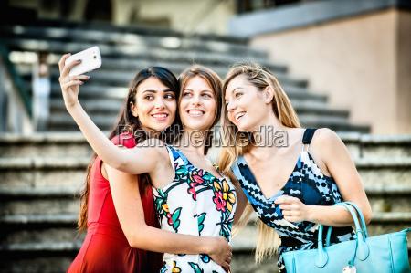 three fashionable young women taking selfie
