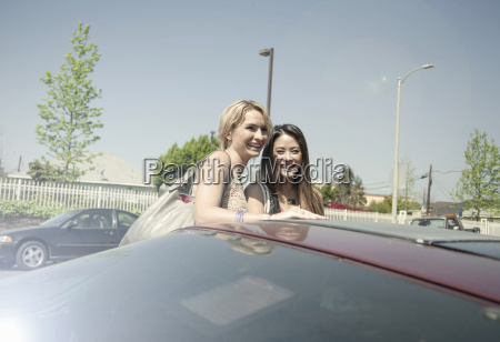 two women laughing standing beside car