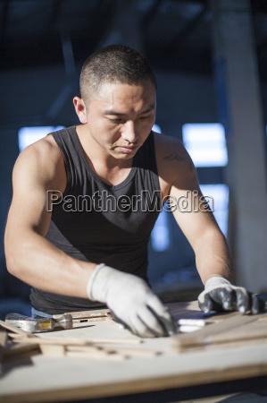 carpenter piecing together wood blocks in