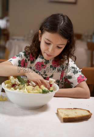 girl eating salad from bowl