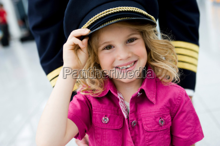 young girl wearing flight captains hat