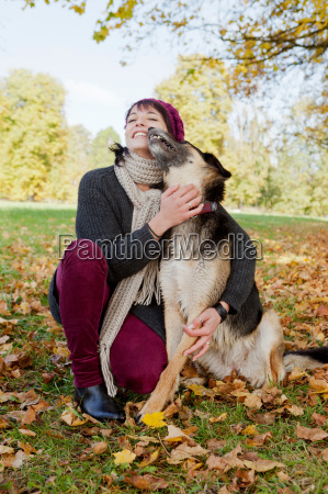 smiling woman petting dog in park